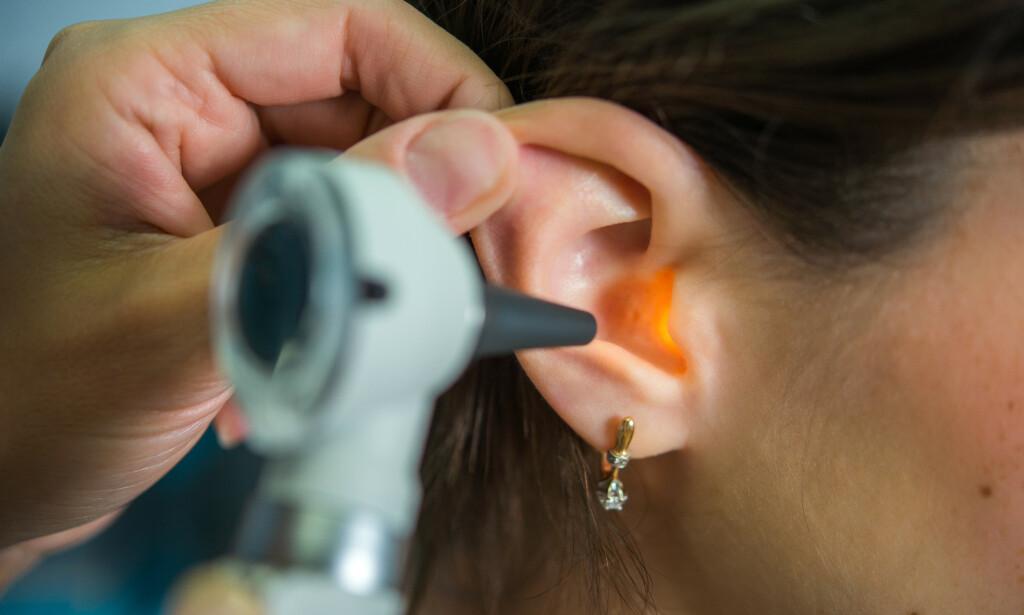 UNDERSØKELSE AV ØRET: En lege undersøker øret ved hjelp av en ørekikkert, såkalt otoskopi. Kan avdekke tegn på både øregangsbetennelse og mellomørebetennelse. Foto: NTB / Shutterstock.